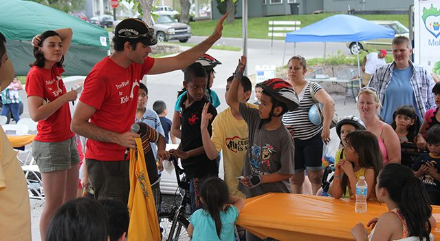 Image of neighborhood bike event with adults and children.